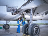 Engineers recycling aircraft parts from airplane on runway - CUF38325