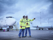 Airport workers in discussion on runway - CUF38328