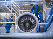 Engineers working on aircraft engine in aircraft maintenance factory - CUF38334