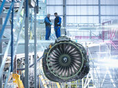 Aircraft engineers standing on wing with jet engine in aircraft maintenance factory - CUF38337
