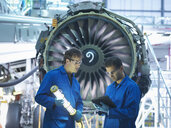 Aircraft engineers discussing maintenance details on digital tablet in front of jet engine in aircraft maintenance factory - CUF38340
