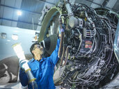 Engineer inspecting jet engine in aircraft maintenance factory - CUF38343