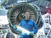Portrait of engineer in front of jet engine in aircraft maintenance factory - CUF38346