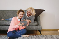 Mother and teenage daughter looking at digital tablet at home - CUF38391