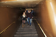 Group of friends coming down stairs into nightclub - CUF38397