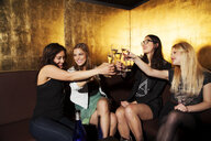 Four female friends toasting with wine in nightclub - CUF38406
