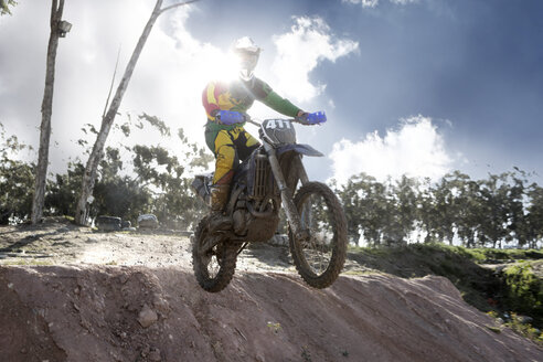 Young male motocross racer jumping mid air down mud hill - CUF38532