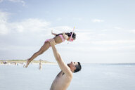 Father holding up snorkeler daughter in sea, Tuscany, Italy - CUF38607