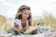 Young woman cross reading a book in beach dunes, Tuscany, Italy - CUF38613