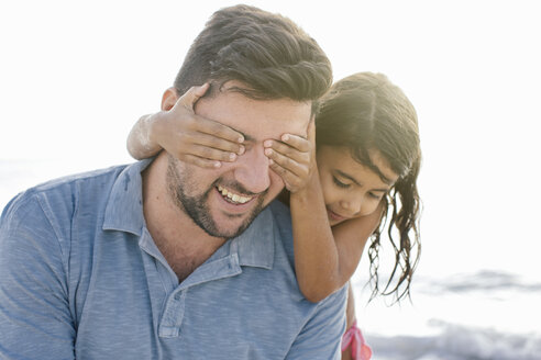 Girl with hands covering fathers eyes on beach, Tuscany, Italy - CUF38619