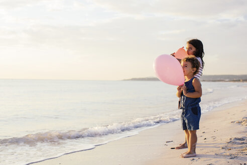 Girl and toddler sister with balloons on beach, Tuscany, Italy - CUF38631