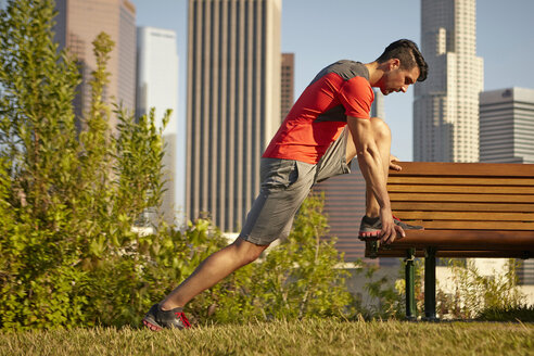Young male runner stretching on park bench - ISF15370