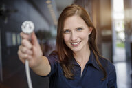 Young businesswoman holding up network power cable in office - ISF15442