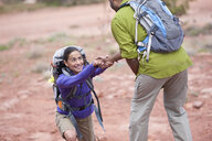 Young man giving helping hand to girlfriend whilst hiking, Sedona, Arizona, USA - ISF15508