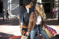 Smiling young woman and boyfriend leaning on bicycle, Cape Town, South Africa - ISF15529
