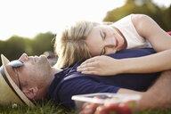 Couple lying asleep in park - ISF15565