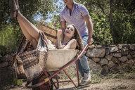 Young man pushing girlfriend in wheelbarrow, Castiadas, Sardinia, Italy - ISF15595