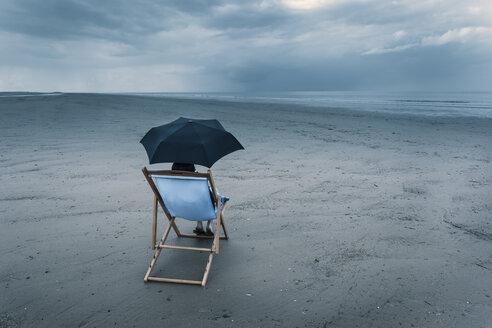 Mature woman sitting on deck chair on stormy beach, under umbrella - CUF38656
