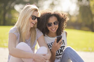 Two young female looking down at text message on smartphone in park - CUF38671