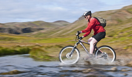 Young male mountain biker speed cycling through hot river,  Reykjadalur valley, South West Iceland - CUF38701