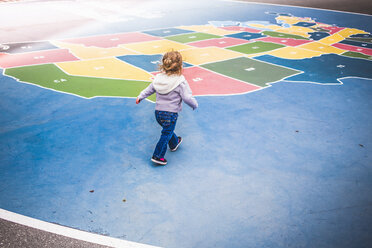 Toddler walking over map of USA in playground - ISF15634
