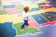 Toddler walking over map of USA in playground - ISF15637