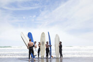 Group of male and female surfer friends standing on beach with surf boards - ISF15646