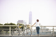 Mid adult female cyclist gazing at city from riverside, New York City, USA - ISF15673
