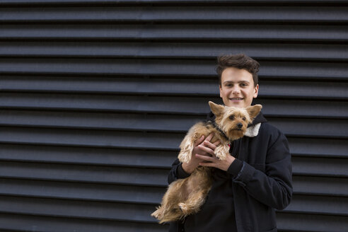 Portrait of smiling teenage boy with his dog against black background - JUNF01063