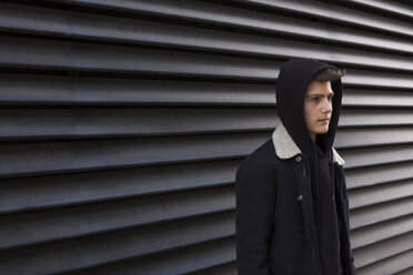 Serious teenage boy wearing hooded jacket standing in front of black background - JUNF01066