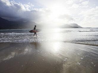 USA, Hawaii, Kauai, Hanalei Bay Resort, man on the beach with surfboard - CVF00924
