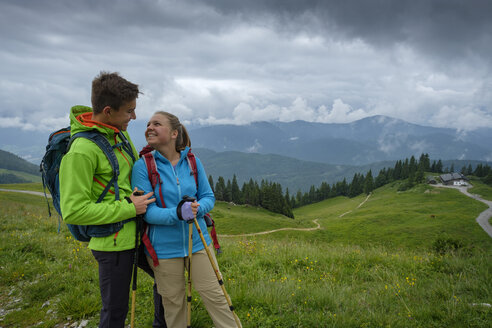 Germany, Lenggries, happy young couple with hiking poles and backpacks on Alpine meadow - LBF02002
