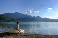 Germany, Bavaria, Upper Bavaria, Heimgarten, teenage girl leaning on boat at Kochelsee - LBF02005