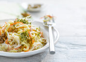 Noodle salad with carrot, walnut and cress on plate - KSWF01956