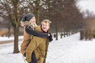 Happy young man giving his girlfriend a piggyback ride - WPEF00570
