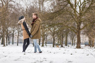 Young couple in love standing hand in hand in a park in winter - WPEF00576