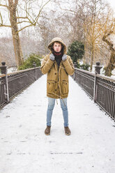 Young man standing on footbridge in a park on a snowy day - WPEF00582
