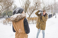 Young man taking picture of his girlfriend in park on a snowy day - WPEF00585
