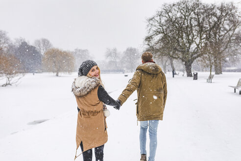 Happy teenage girl strolling with her boyfriend in park on snow day - WPEF00588
