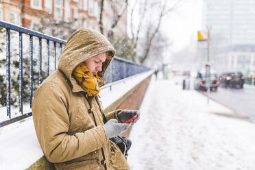 Young man using cell phone outdoors on a snowy day - WPEF00591