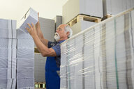 Factory worker moving and stacking cardboard - CUF38777