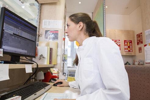 Pharmacist in pharmacy using desktop computer - CUF38789
