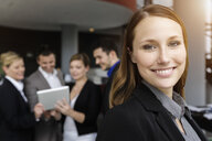 Smiling businesswoman, colleagues in background using digital tablet - CUF38810