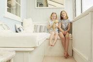 Portrait of two sisters sitting in holiday apartment porch - CUF38828