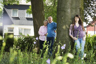 Grandparents and granddaughter standing by tree - CUF38834