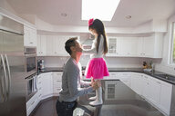 Portrait of mature man with daughter standing on kitchen island - ISF15799