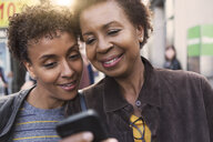 Close up of two mature female friends reading smartphone texts on street - ISF15811