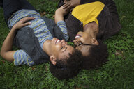Two mature female friends lying on park grass - ISF15814