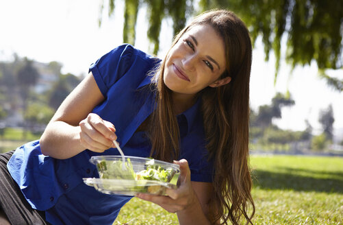 Woman eating salad in park - ISF15820