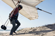 Man carrying hang glider on beach - ISF15898